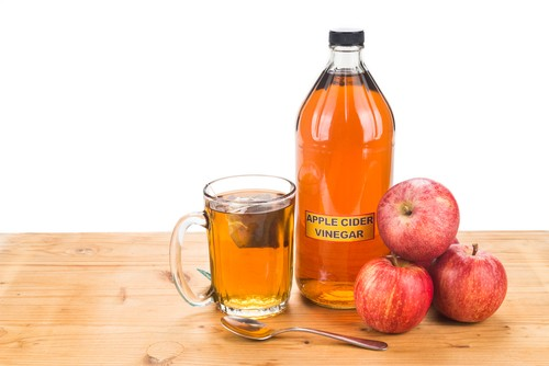 bottle of apple cider vinegar with apples and glass next to it