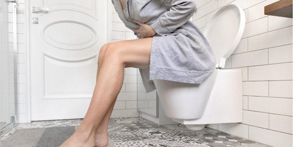 women sitting in pain on toillet seat