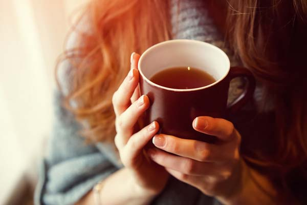 A girl holding a cup of tea