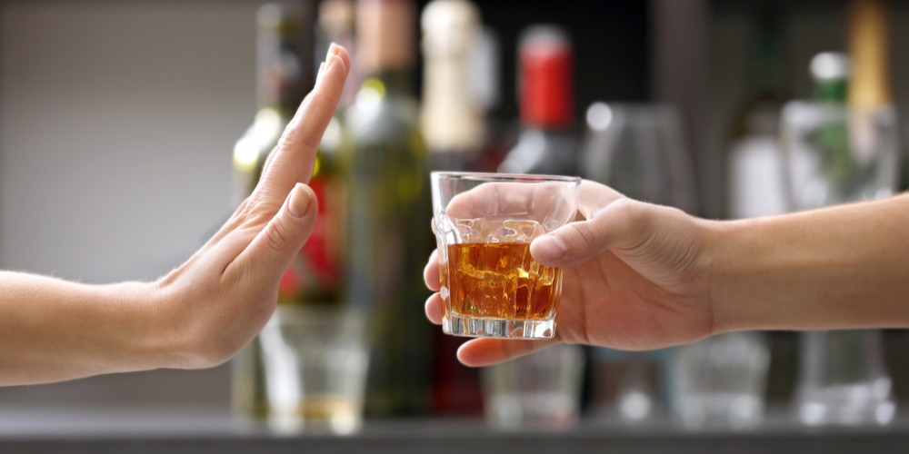 female saying no to alcohol