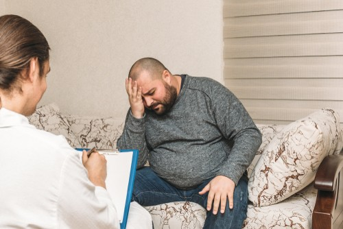 fat man sitting worried at a doctor's clinic