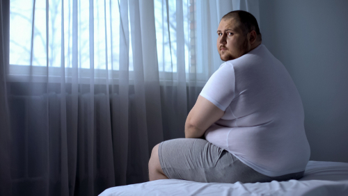 fat man sitting on bed
