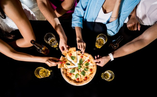 pizza and hard drinks kept on a table with people around