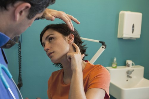 ENT specialist checking a woman's ear