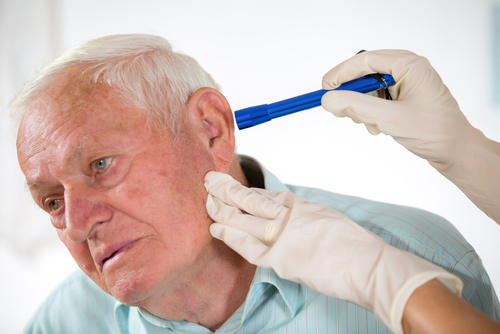 ENT doctor checking an old man's ear