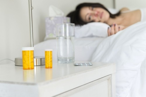 woman resting on bed with medicines next to the bed on the table