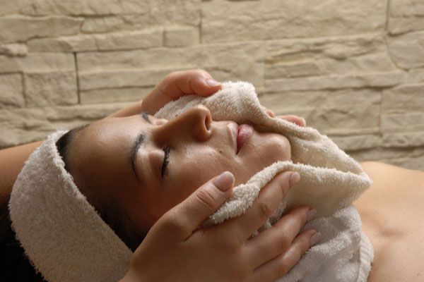 Girl with eyes closed with warm towel on face