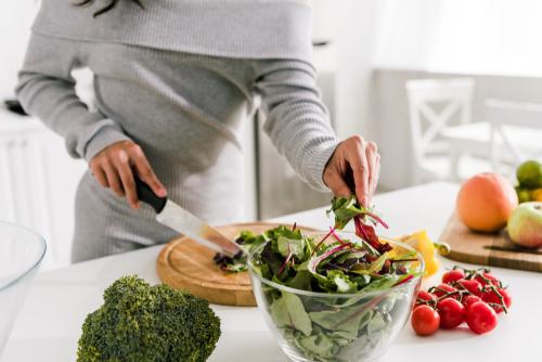 woman cutting green vegetables