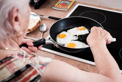 old woman eating eggs