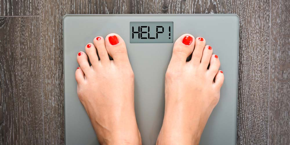 female on a weighing machine with help written!- showing the concept of weight gain