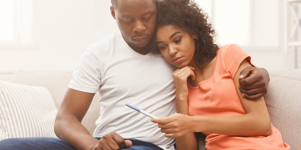 stressed couple holding negative pregnancy test