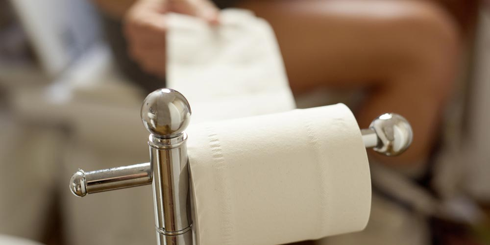 man on toilet seat troubles with constipation
