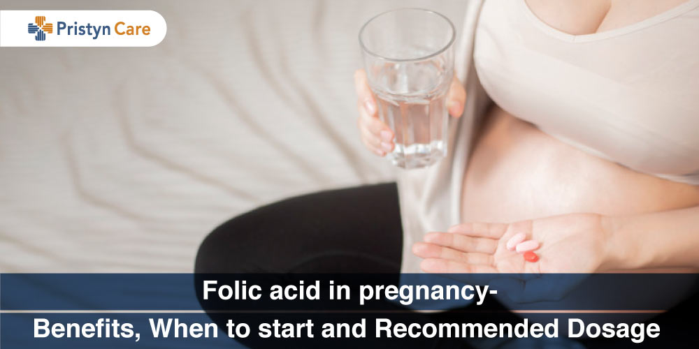 pregnant female holding folic acid supplement in hand