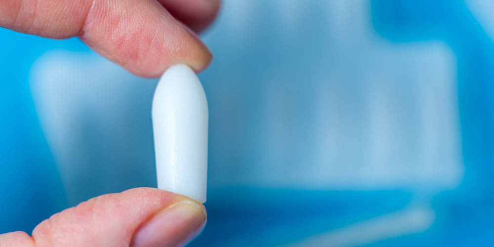 female holding vaginal suppository or vaginal capsule in hand